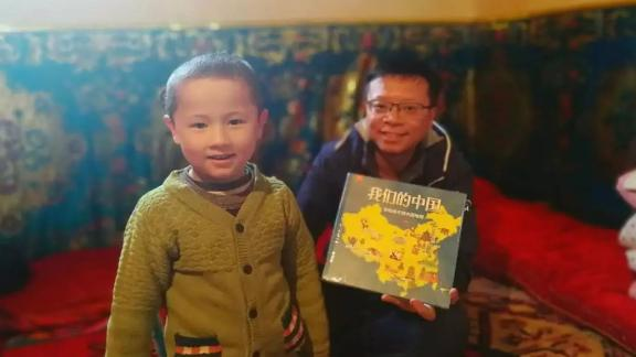 """A civilian worker presents a Uyghur child whom he has been assigned to treat as his """"relative"""" with a picture book titled Our China, in an undated photo from Xinjiang"""