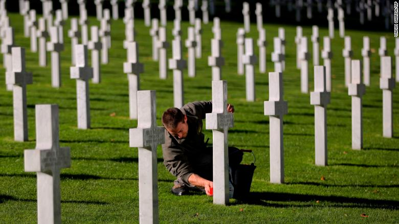 A cemetery employee cleans the cross Friday of an American serviceman killed during World War I, ahead of centenary events at the American Cemetery in Suresnes.