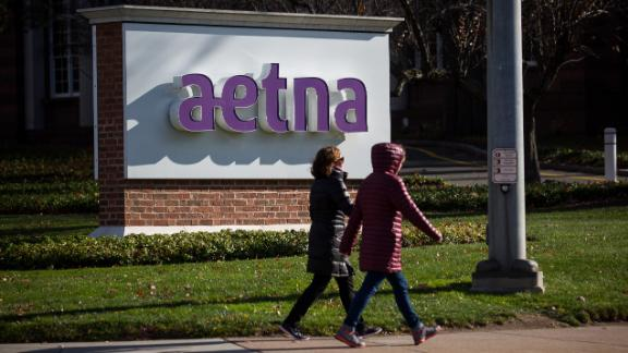 Pedestrians walk past signage Aetna Inc. headquarters in Hartford, Connecticut, U.S., on Tuesday, Nov. 22, 2016. The Justice Department sued to block the union of Aetna Inc. and Humana Inc., saying they would reduce the number of large, national health care insurance providers, leading to increased costs for their clients. Photographer: Michael Nagle/Bloomberg via Getty Images