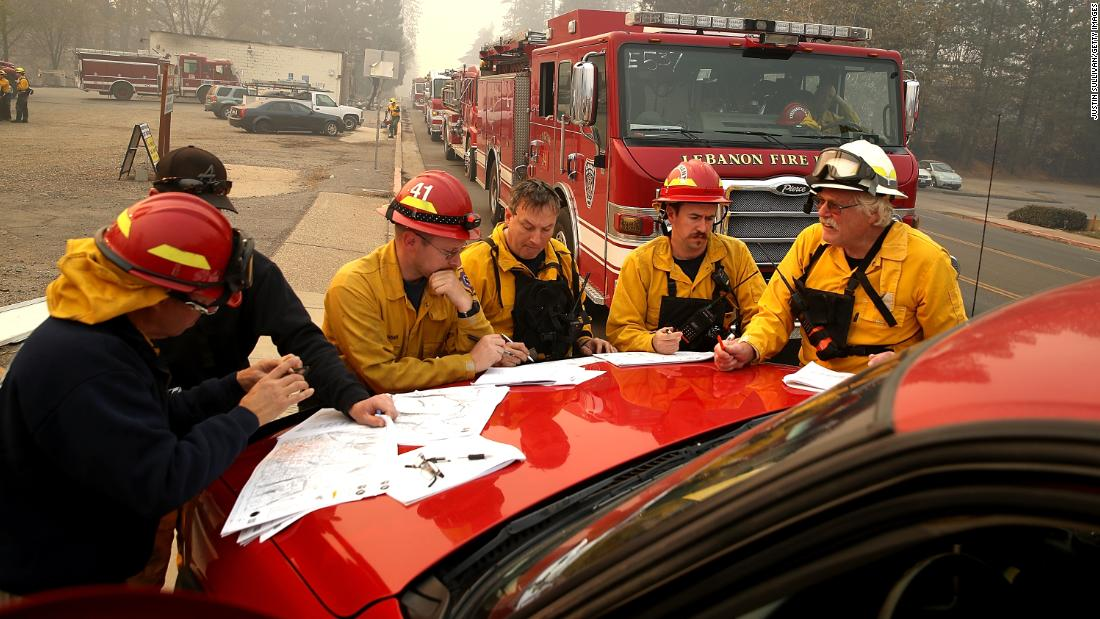 Firefighters hold a morning meeting as they continue to battle the Camp Fire, in Paradise, California. The fire was at 20% containment on November 10.
