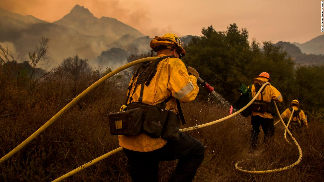 Los Angeles County firefighters fight  flames approaching the Salvation Army camps in Malibu Creek State Park during the Woolsey Fire on November 10.