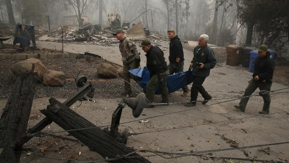 PARADISE, CA - NOVEMBER 10:  Yuba and Butte County sherriff deputies carry a body bag with a deceased victim of the Camp Fire on November 10, 2018 in Paradise, California. Fueled by high winds and low humidity, the rapidly spreading Camp Fire ripped through the town of Paradise and has quickly charred 100,000 acres and has destroyed over 6,700 homes and businesses in a matter of hours. The fire is currently at 20 percent containment.  (Photo by Justin Sullivan/Getty Images)