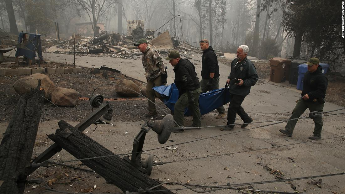 Yuba and Butte County sheriff deputies carry a body bag with a victim of the Camp Fire on November 10 in Paradise, California.