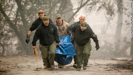 Deputies carry a body away from a burned residence in Paradise, California on Saturday.