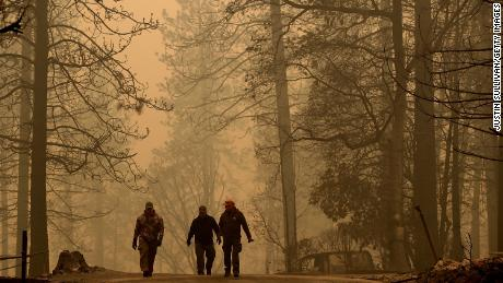 Sheriff deputies walk through a neighborhood destroyed by the Camp Fire on November 10, 2018 near Paradise, California.