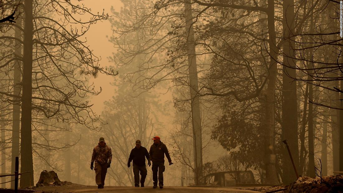 Sheriff's deputies on Saturday walk through a neighborhood destroyed by the Camp Fire near Paradise.