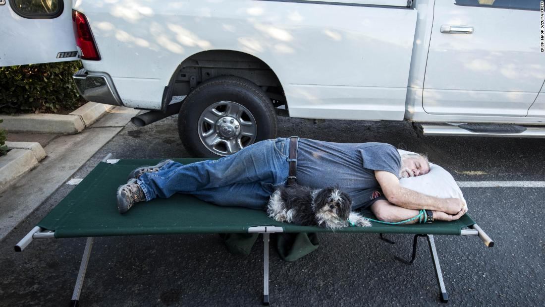 Doug Thomas and his dog Hanna rest Friday while they await word if they can return to their Malibu Lake home.