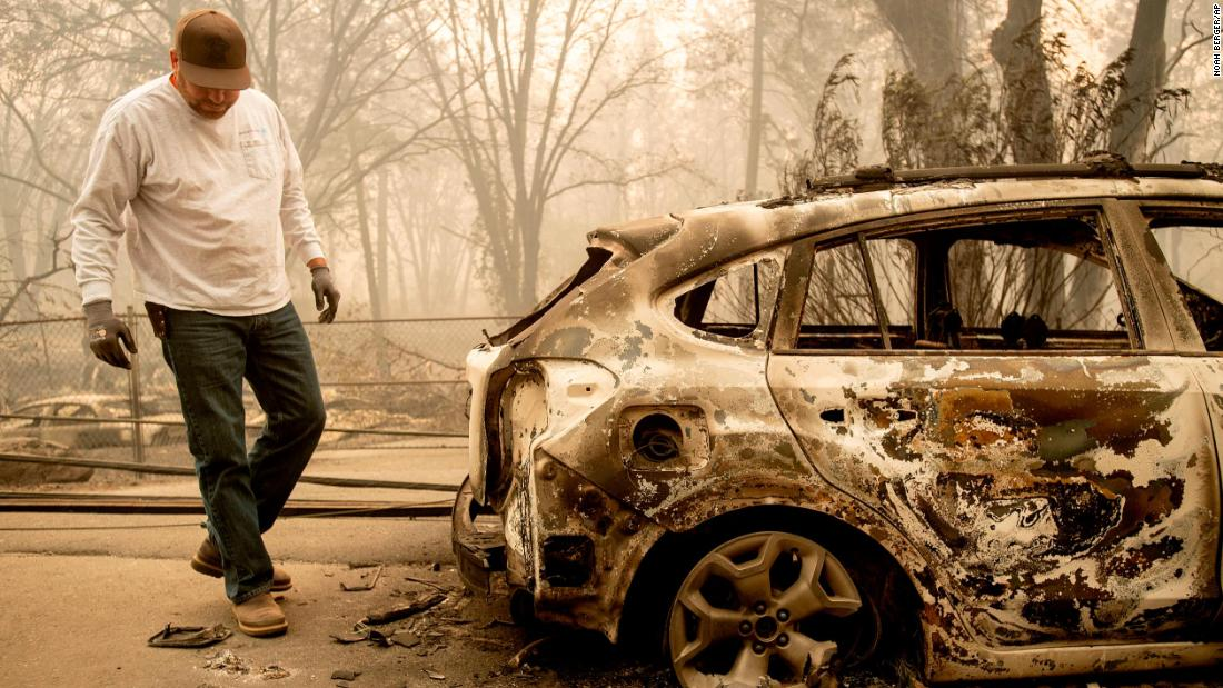 Eric England searches through a friend's vehicle Saturday after the wildfire burned through Paradise.