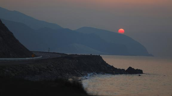 The sun rises over the Pacific Ocean on November 11 as the Woolsey Fire burns in Malibu.