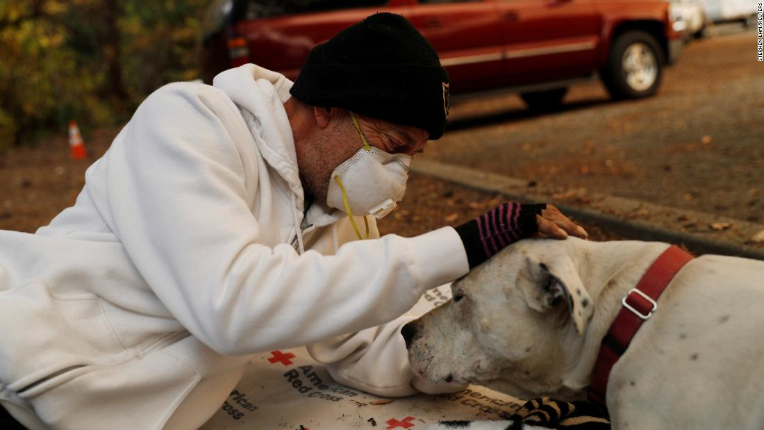 Evacuee Brian Etter and his dog Tone, who walked on foot to escape the Camp Fire, rest in the parking lot of Neighborhood Church of Chico on November 11 in Chico, California.