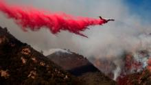A plane drops fire retardant on a burning hillside Sunday, Nov. 11, 2018, in Malibu, Calif. (AP Photo/Jae C. Hong)