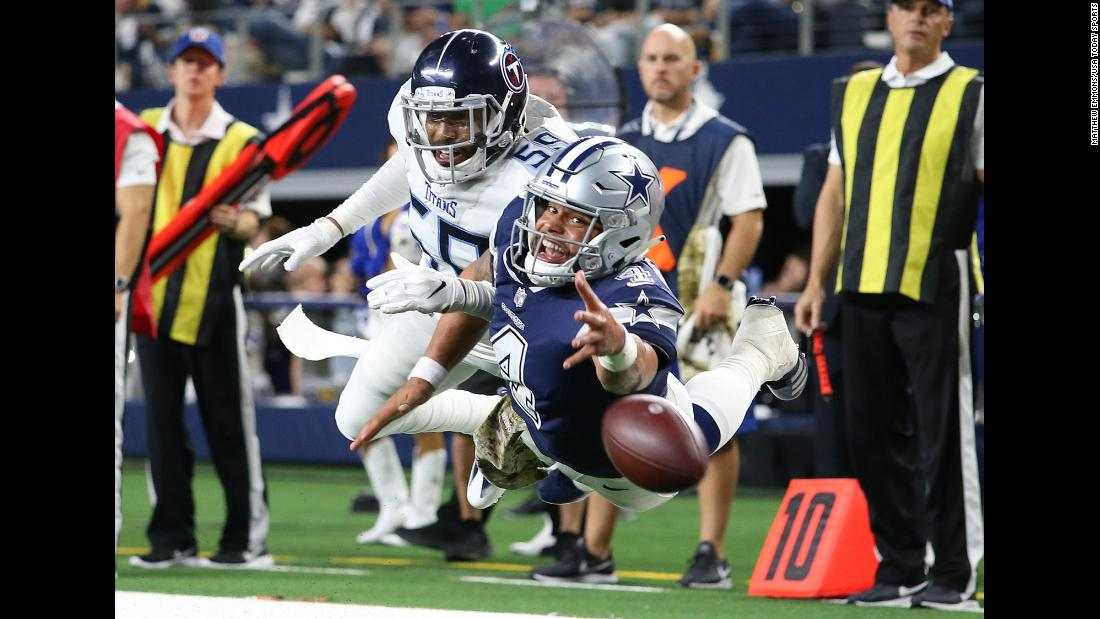 Dallas Cowboys quarterback Dak Prescott, defended by Tennessee Titans linebacker Wesley Woodyard, dives for a pass thrown by Cowboys wide receiver Cole Beasley in the fourth quarter at AT&T Stadium in Arlington, Texas on November 5. The Cowboys ultimately fell to the Titans 28-14.