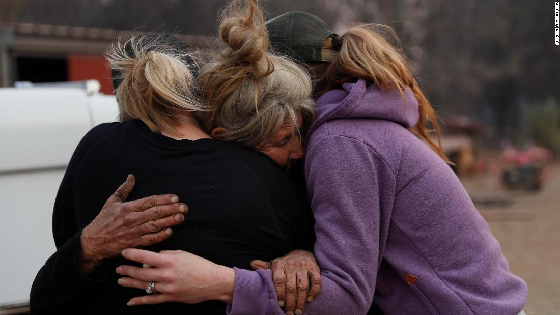 Cathy Fallon, center, who stayed behind to tend to her horses during the Camp Fire in Paradise, embraces Shawna De Long, left, and April Smith, who brought supplies for the horses.