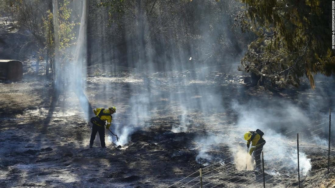 Firefighters douse burning embers off a canyon road which cuts across the mountains to Malibu, California, on November 11.