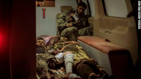 Two SDF soldiers await transfer to a hospital alongside the body of one their fallen comrades (bottom center) in an ambulance in Sousa, on October 25.