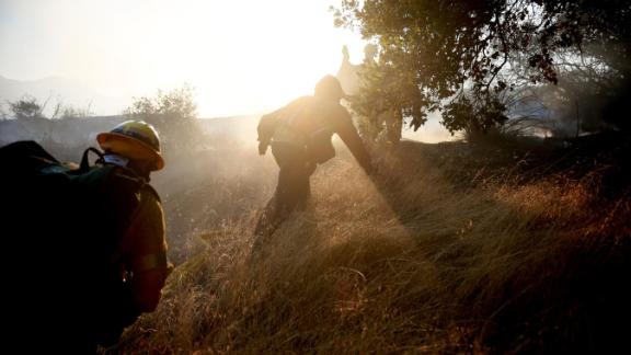 Firefighters battle a blaze in Malibu on Saturday, November 10.