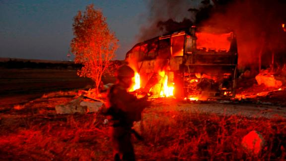 Israeli security forces and firefighters gather near a bus hit by a rocket fired from Gaza.
