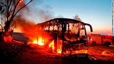 A bus set ablaze after it was hit by a rocket fired from the Gaza Strip, at the Israel-Gaza border near Kfar Aza.