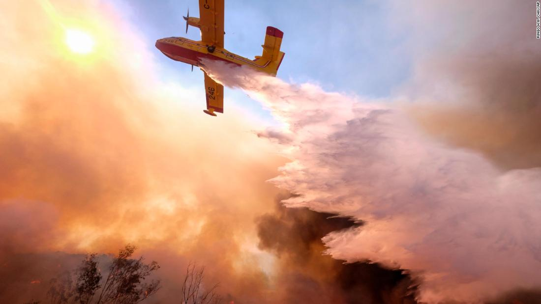 An air tanker drops water on a fire along the Ronald Reagan Freeway in Simi Valley, California, on Monday, November 12.