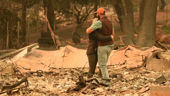 Chris and Nancy Brown embrace while looking over the remains of their home on November 12.