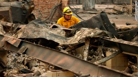 A firefighter looks through a destroyed home in Paradise.
