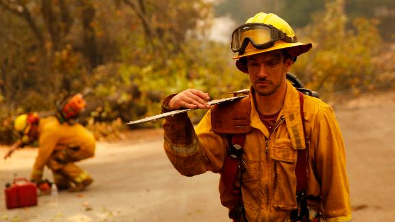 Shawn Slack carries a chainsaw on November 12 after trees burned in Paradise.