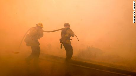 Firefighters battle a fire along the Ronald Reagan (118) Freeway in Simi Valley, Calif., Monday, Nov. 12, 2018. (AP Photo/Ringo H.W. Chiu)
