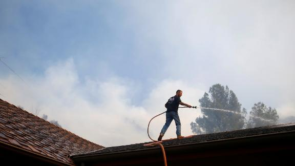 A resident sprays down a roof as firefighters battle the Peak Fire in Simi Valley.