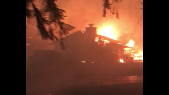 As Brad Weldon tried to use a garden hose to keep flames away from his home in Paradise, California, a neighbor's house burned to the ground.