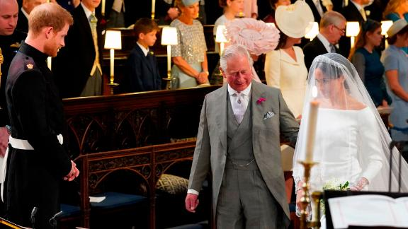Prince Charles accompanies his future daughter-in-law, Meghan Markle, as she is married to Prince Harry in May 2018.