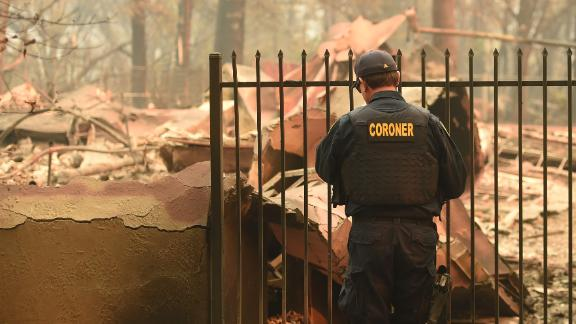 An Alameda County coroner looks for human remains at a burned home in Paradise, California.