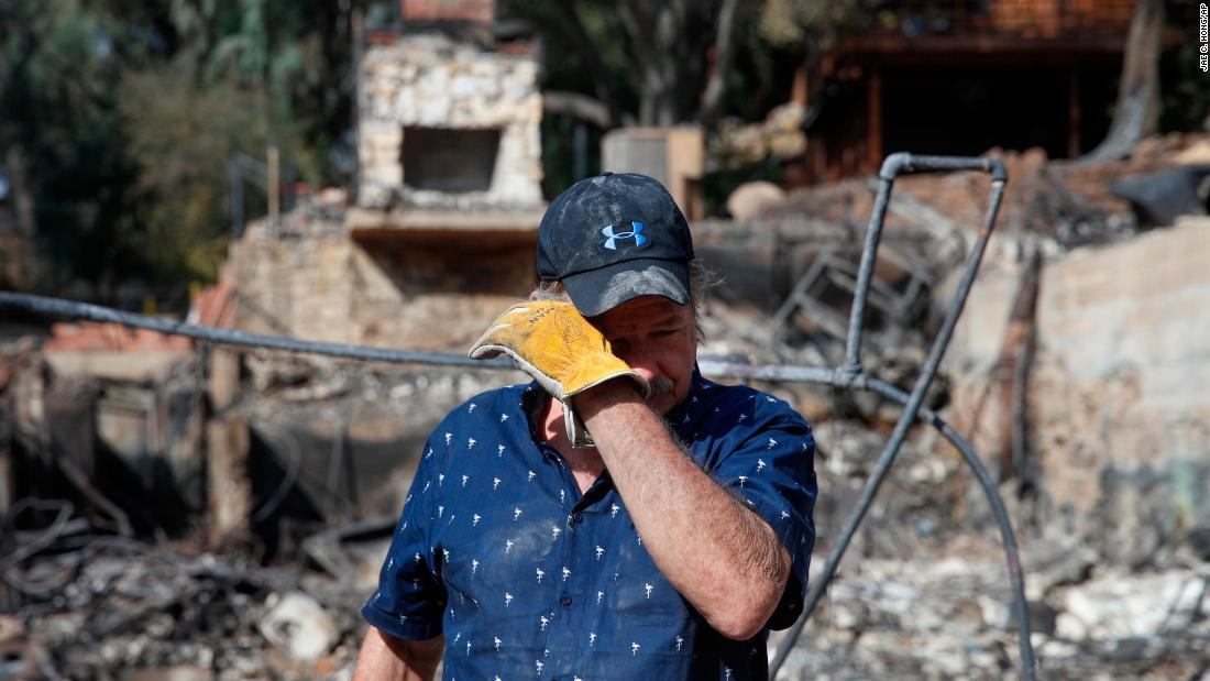 Roger Kelton, 67, wipes away tears on November 13, while searching through the remains of his mother-in-law's home destroyed by the Woolsey Fire in Agoura Hills.
