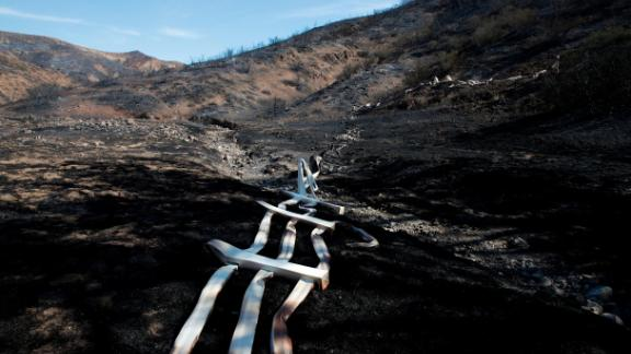 A melted fence runs along a hillside as firefighters battle the Woolsey Fire in Agoura Hills on November 13.