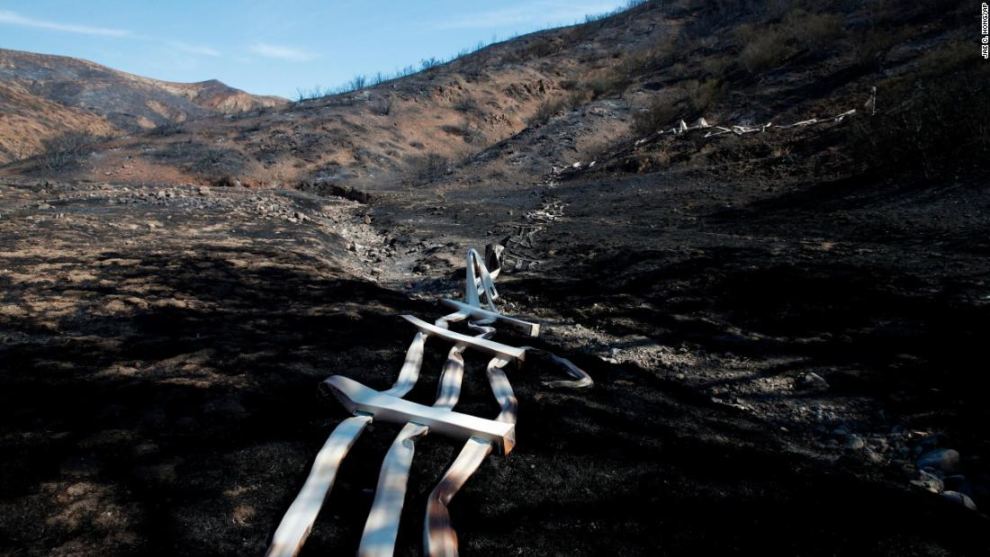 A melted fence runs along a hillside as firefighters continue to battle the Woolsey Fire burning in Agoura Hills, on November 13.