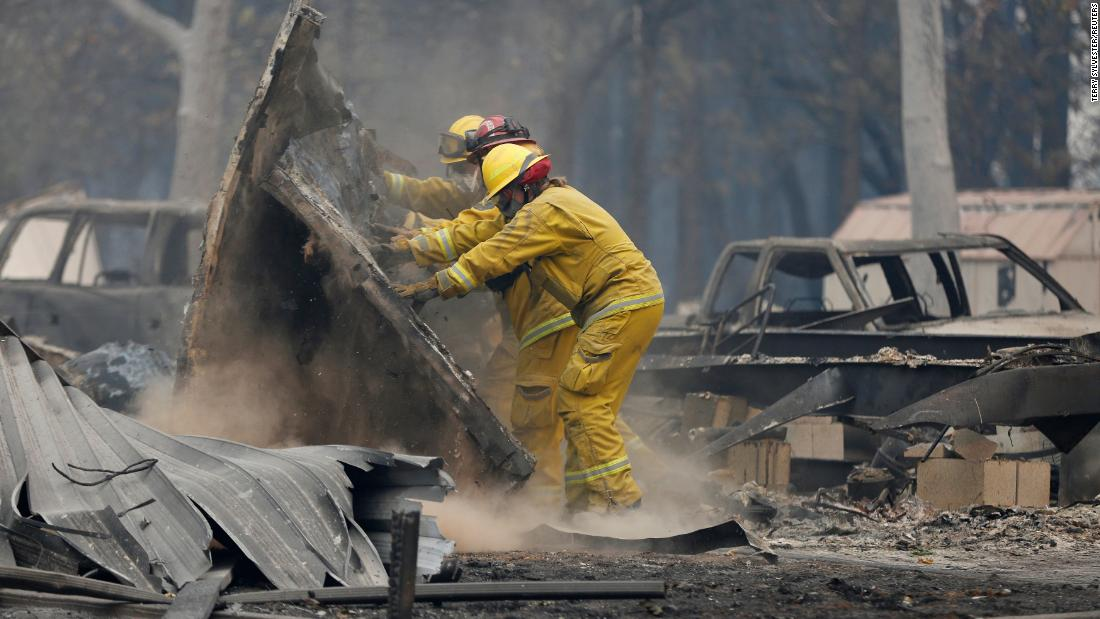 Firefighters search through the remains of a house destroyed by the Camp Fire in Paradise, on November 13.