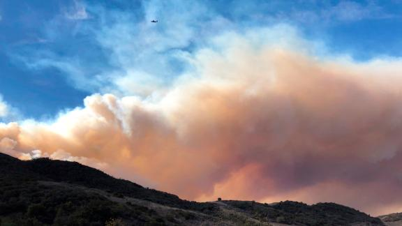 Smoke fills the horizon on November 13 as an airplane flies near a flare-up of the Woolsey Fire near Lake Sherwood.