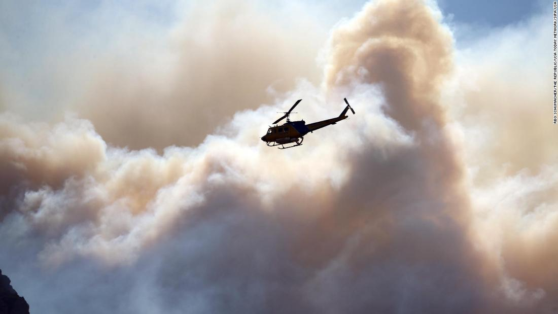 A helicopter flies near the Woolsey Fire burning in the Santa Monica Mountains National Recreation Area on Tuesday, November 13.