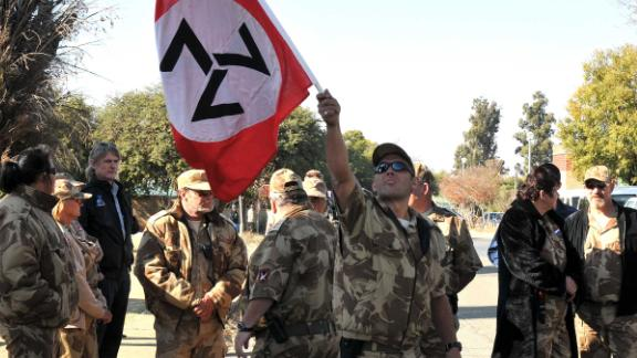 Supporters of the white supremacist Afrikaner Resistance Movement (AWB) stand outside the Ventersdorp Magistrate court on May 22, 2012 as they wait for the verdict of the murder of their leader Eugene Terre'Blanche. Terre'Blanche, the co-founder of the far-right AWB, was bludgeoned to death at his farmhouse outside the small northwestern town of Ventersdorp on April 3, 2010. His former employees Chris Mahlungu, 29, and an 18-year-old youth are charged with murder, attempted robbery and house breaking and aggravated robbery. The two have pleaded not guilty to all the charges and they opted not to testify in a trial punctuated by shocking claims of sexual and physical abuse . AFP PHOTO / STRINGER        (Photo credit should read STRINGER/AFP/GettyImages)