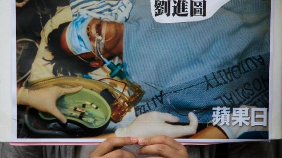 A protester holds a sign showing Ming Pao editor Kevin Lau in hospital after he was attacked in 2014.