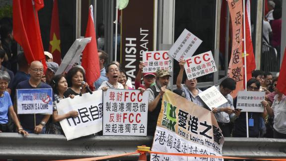 People raise pro-China signs in a protest against Hong Kong independence in front of the Foreign Correspondents' Club in Hong Kong on August 14, 2018.