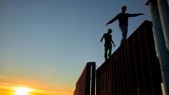 Two Central American migrants walk along the top of the border structure separating Mexico and the United States on Wednesday in Tijuana.