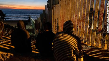 "TOPSHOT - Central American migrants moving towards the United States in hopes of a better life, are seen near the US-Mexico border fence in Playas de Tijuana, Mexico, on November 14, 2018. - US Defence Secretary Jim Mattis said Tuesday he will visit the US-Mexico border, where thousands of active-duty soldiers have been deployed to help border police prepare for the arrival of a ""caravan"" of migrants. (Photo by Guillermo Arias / AFP)        (Photo credit should read GUILLERMO ARIAS/AFP/Getty Images)"