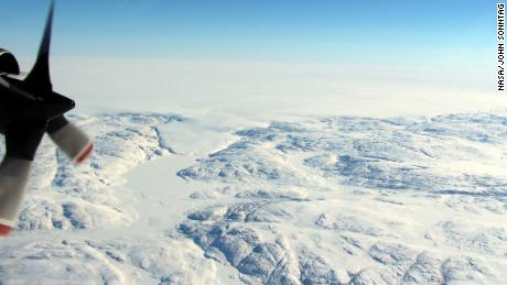 The Hiawatha impact crater is covered by the Greenland Ice Sheet, which flows just beyond the crater rim, forming a semi-circular edge. Part of this edge, seen in the top of the photograph, and a tongue of ice that breaches the crater's rim are shown in this photo taken during a NASA flight in April.