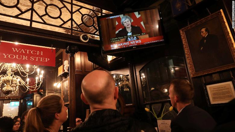 Pubgoers in London watch a broadcast of Theresa May's press conference.