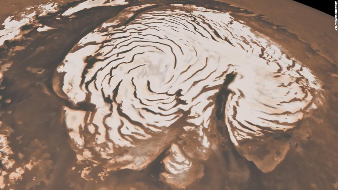 This image, combining data from two instruments aboard NASA's Mars Global Surveyor, depicts an orbital view of the north polar region of Mars. The ice-rich polar cap is  621 miles across, and the dark bands in are deep troughs. To the right of center, a large canyon, Chasma Boreale, almost bisects the ice cap. Chasma Boreale is about the length of the United States' famous Grand Canyon and up to 1.2 miles deep.