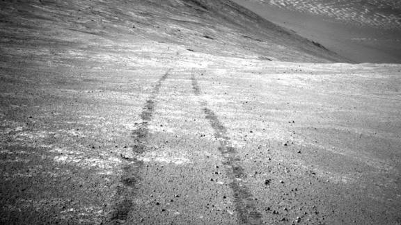 From its perch high on a ridge, Opportunity recorded this image of a Martian dust devil twisting through the valley below. The view looks back at the rover