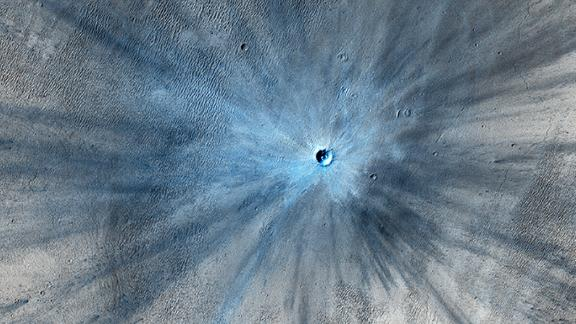 A dramatic, fresh impact crater dominates this image taken by the HiRISE camera on November 19, 2013. The crater spans approximately 100 feet and is surrounded by a large, rayed blast zone. Because the terrain where the crater formed is dusty, the fresh crater appears blue in the enhanced color of the image, due to removal of the reddish dust in that area.