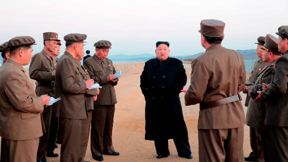 In this undated photo released on Friday by the North Korean government, Kim Jong Un, listens to a military official as he inspects a weapon testing.