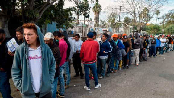 Central American migrants line up for food at a shelter in Playas de Tijuana on Friday.