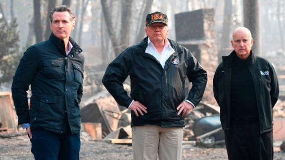 "US President Donald Trump (C) looks on with Governor of California Jerry Brown (R) and Lieutenant Governor of California, Gavin Newsom, as they view damage from wildfires in Paradise, California on November 17, 2018. - President Donald Trump arrived in California to meet with officials, victims and the ""unbelievably brave"" firefighters there, as more than 1,000 people remain listed as missing in the worst-ever wildfire to hit the US state. (Photo by SAUL LOEB / AFP)        (Photo credit should read SAUL LOEB/AFP/Getty Images)"
